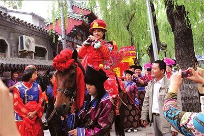 """北京/""""皇帝""""新郎骑着大马,一路上神采奕奕,不停向路人拱手敬礼。"""
